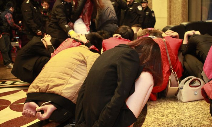 Alleged sex workers and their clients are detained by Chinese police after a raid on an entertainment center in Dongguan, in southern China's Guangdong province on Feb. 9, 2014. The crackdown is not expected to last long. (STR/AFP/Getty Images)