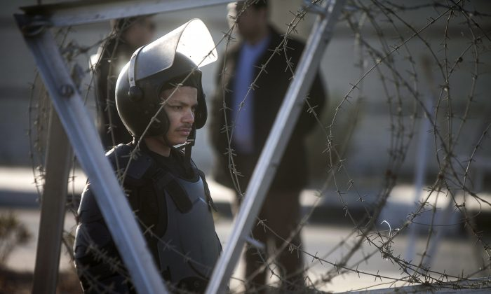 An Egyptian riot policeman stands guard in front of the Police Academy in Cairo on Feb. 5 2014. Egypt's military leaders proclaim an allegiance to the democratic process, but their actions say otherwise. (Mahmoud Khaled/AFP/Getty Images)