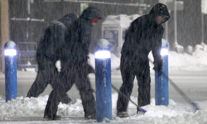 Workers clears snow from the sidewalk outside a business Saturday, Feb. 15, 2014, in the Boston suburb of Hudson, Mass. (AP Photo/Bill Sikes)