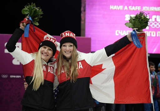 Gold medal winners from Canada Kaillie Humphries, left, and Heather Moyse hold the flag after the women's bobsled competition at the 2014 Winter Olympics, Wednesday, Feb. 19, 2014, in Krasnaya Polyana, Russia. (AP Photo/Jae C. Hong)