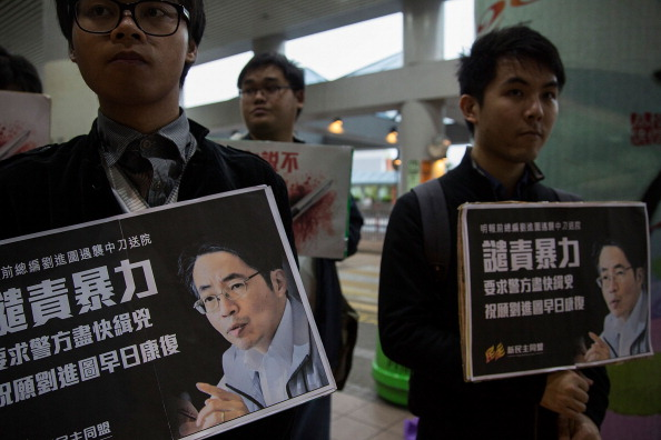 Pro-democracy activists hold a banner with an image of Kevin Lau Chun-to, former chief editor of the Ming Pao newspaper, as they attend a candlelight vigil. Lau was stabbed and seriously injured by two attackers on Feb. 26. (Lam Yik Fei/Getty Images)
