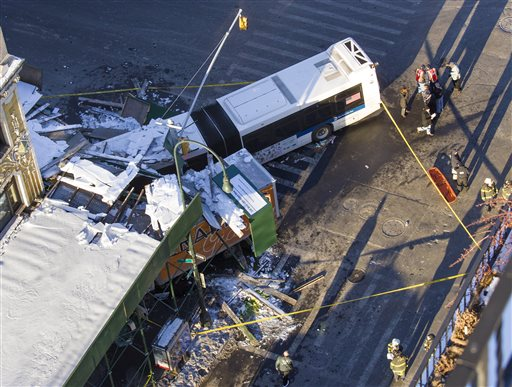 A Metropolitan Transportation Authority bus and a truck rest against scaffolding at 14th Street and 7th Avenue in New York, Wednesday, Feb. 12, 2014, after an early morning collision between the bus and truck. One person was killed and at least four were injured in the crash. (AP Photo/Craig Ruttle)