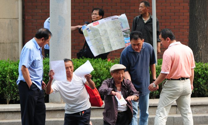 Elderly petitioners protesting medical access and land grab issues are detained by police in Beijing on May 10, 2012. New regulations that restrict petitioners have not been well received. (Mark Ralston/AFP/Getty Images)