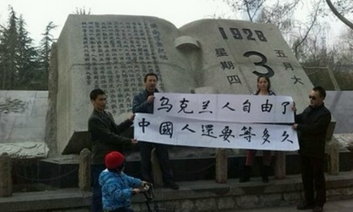 "Four people hold banners saying, ""Ukrainian people are free now. How long do Chinese people have to wait?"" in China, February 2014. The downfall of the Ukrainian government came as happy news to many Chinese. (Weibo.com)"
