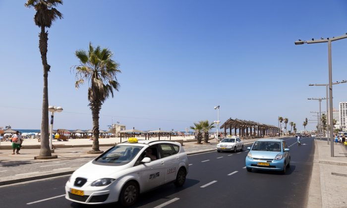 Taxi cabs and a random vehicle driving along the beach on a summer day in Tel Aviv. (*Shutterstock)