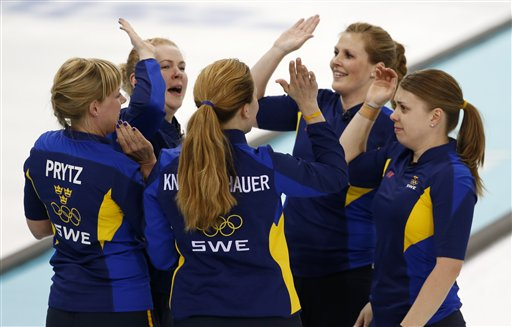 Sweden players, clockwise from left, Maria Prytz, Margaretha Sigfridsson, Christina Bertrup, Maria Wennerstroem and coach Agnes Knochenhauer celebrate their victory over Switzerland in the women's curling semifinal game against at the 2014 Winter Olympics, Wednesday, Feb. 19, 2014, in Sochi, Russia. (AP Photo/Robert F. Bukaty)