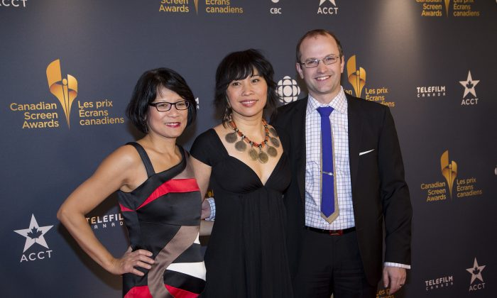 """MP Olivia Chow (L) poses with her stepson Mike Layton and actress Sook-Yin Lee. Lee was honoured with Best Actress in a Dramatic Program or Mini-Series for playing Chow in """"Jack,"""" a biopic about late NDP leader Jack Layton, Chow's husband. In the press room, Lee spoke of the challenges and rewards of playing a real-life person who was there to guide her on set. She admitted this was intimidating, but noted that Chow was also very generous. """"She's an artist herself, and gave me a lot of room to interpret."""" The actress said she set out to exteriorize Chow's inner world, but ended up putting so much into the role that she had to stop and question who she was.""""It becomes very clear that personality is a construct."""" Lee also noted it was both a challenge and a gift to portray the loss of a beloved person, an inevitable yet difficult part of life. """"It was very visceral to be able to walk through that and do it in a safe place—not just in crazy chaotic life, but in a fictional scenario. It was really good therapy,"""" she said. (Evan Ning/Epoch Times)"""