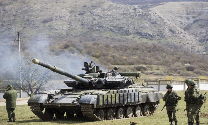Russian soldiers stand near a tank at a former Ukrainian military base in Perevalne, outside Simferopol, Crimea, March 27, 2014. (AP Photo/Pavel Golovkin)
