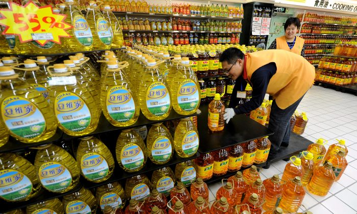 Chinese workers place bottles of cooking oil at a supermarket in Hefei, east China's Anhui province in this file photo. (STR/AFP/Getty Images)