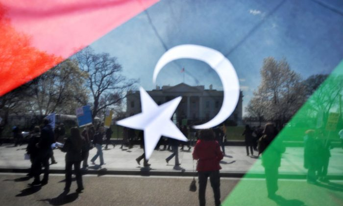 A man waves a Kingdom of Libya flag during an anti-war demonstration in front of the White House in Washington, DC, on March 26, 2011 urging an end to the war on Libya. (Jewel Samad/AFP/Getty Images)