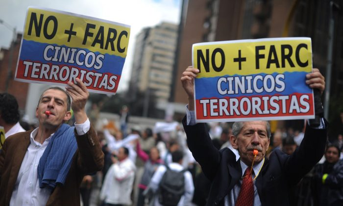 Colombians protest in Bogota, on December 6, 2011, against the left-wing FARC narcoguerrilla and their killing of hostages during a recent firefight with governmental forces. The placards read 'No More FARC', 'Cynical Terrorists'. (Eitan Abramovich/AFP/Getty Images)