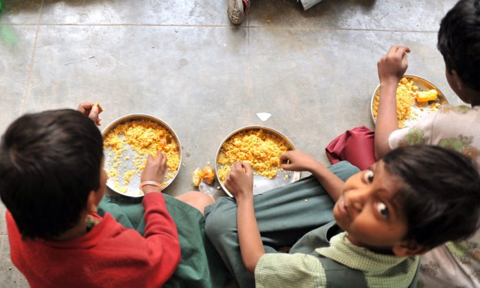 Indian children eat their mid-day meal at a Government High School in Hyderabad, on January 10, 2012. Levels of under-nutrition in the country were 'unacceptably high' despite impressive GDP growth, Prime Minister Manmohan Singh said on January 10, 2012 and added that the problem of malnutrition was a 'national shame'. (Noah Seelam/AFP/Getty Images)