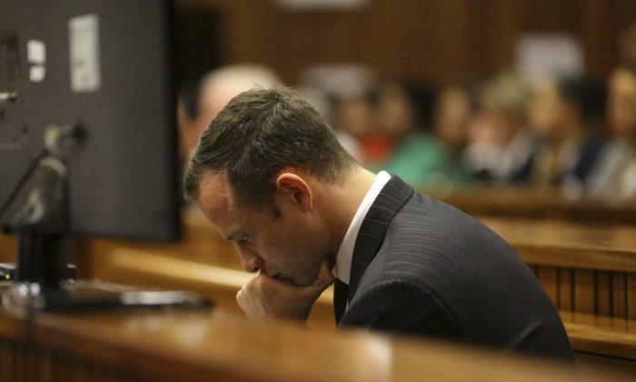 Oscar Pistorius sits in the dock as he listens to cross questioning about the events surrounding the shooting death of his girlfriend Reeva Steenkamp, in court during his trial in Pretoria, South Africa, Monday, March 10, 2014. The testimony in the first week of Pistorius' murder trial was jaw dropping at times, and more riveting evidence is expected as the prosecution seeks to prove beyond reasonable doubt that the double-amputee athlete intentionally shot dead Steenkamp, on Valentines Day in 2013. (AP Photo/Siphiwe Sibeko, Pool)