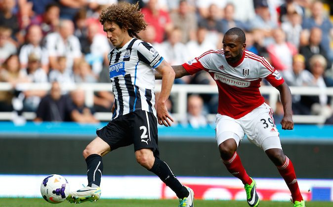 Fabricio Coloccini (L) of Newcastle in action with Darren Bent of Fulham during the Premier League match between Newcastle United and Fulham at the St James Park on August 31, 2013 in Newcastle-Upon-Tyne, England. (Photo by Paul Thomas/Getty Images)