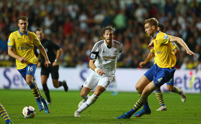 Michu (C) of Swansea City passes as Per Mertesacker (R) of Arsenal closes in during the Barclays Premier League match between Swansea City and Arsenal at the Liberty Stadium on September 28, 2013 in Swansea, Wales. (Photo by Michael Steele/Getty Images)