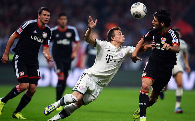 Xherdan Shaqiri of Muenchen is challenged by Emir Spahic of Leverkusen during the Bundesliga match between Bayer Leverkusen and FC Bayern Muenchen at BayArena on October 5, 2013 in Leverkusen, Germany. (Photo by Lars Baron/Bongarts/Getty Images)