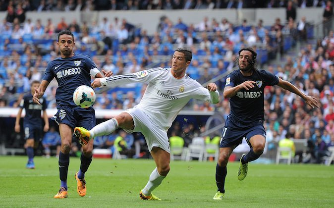 Cristiano Ronaldo (C) of Real Madrid CF is tackled by Wellington Silva (L) and Sergio Sanchez of Malaga CF during the La Liga match between Real Madrid CF and Malaga CF at the Santiago Bernabeu stadium on October 19, 2013 in Madrid, Spain. (Photo by Denis Doyle/Getty Images)