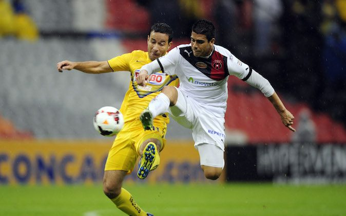 Gabriel Rey (L) of America from Mexico vies for the ball with Ariel Rodriguez (R) of Alajuelense from Costa Rica, during their Concacaf 2013 tournament, in Mexico City, on October 22, 2013. (ALFREDO ESTRELLA/AFP/Getty Images)
