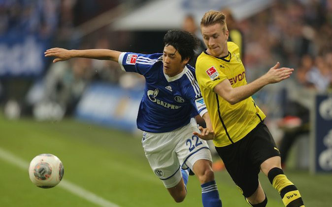 Atsuto Uchida of Schalke (L) and Marco Reus of Dortmund fight for the ball for the ball during the Bundesliga match between Schalke 04 and Borussia Dortmund at Veltins-Arena on October 26, 2013 in Gelsenkirchen, Germany.  (Photo by Juergen Schwarz/Bongarts/Getty Images)