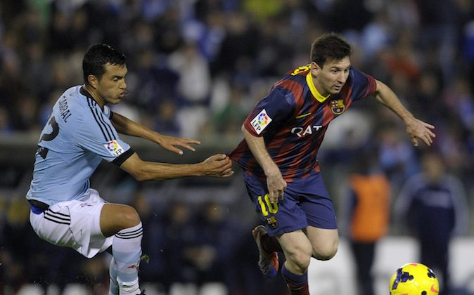 : Barcelona's Argentinian forward Lionel Messi (R) vies with Celta's Argentinian defender Gustavo Cabral during the Spanish league football match RC Celta de Vigo vs FC Barcelona at the Balaidos stadium in Vigo on October 29, 2013. Barcelona won the match 3-0. (MIGUEL RIOPA/AFP/Getty Images)