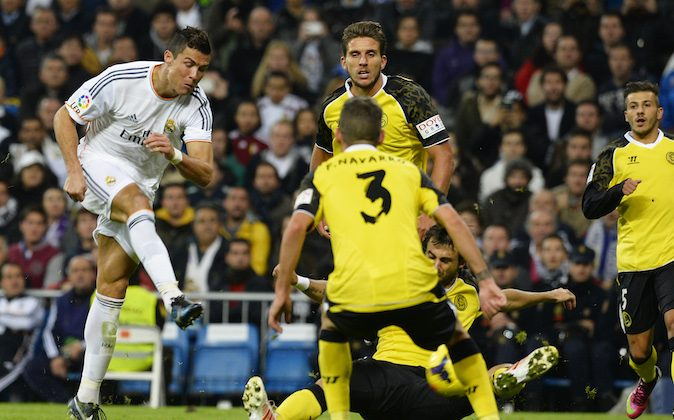 Real Madrid's Portuguese forward Cristiano Ronaldo (L) scores during the Spanish league football match Real Madrid CF vs Sevilla FC at the Santiago Bernabeu stadium in Madrid on October 30, 2013. (GERARD JULIEN/AFP/Getty Images)