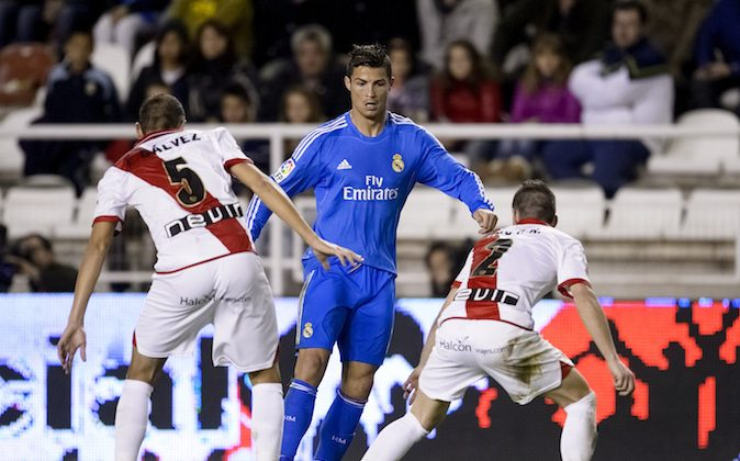 Real Madrid's Portuguese forward Cristiano Ronaldo vies with Rayo Vallecano's defender Alejandro Galvez during the Spanish league football match Rayo Vallecano vs Real Madrid at the Vallecas stadium in Madrid on November 2, 2013. Real Madrid won 3-2. (DANI POZO/AFP/Getty Images)