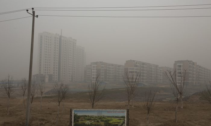 In this photo taken Wednesday, Feb. 26, 2014, an artistic rendering functioning as an advertisement of a residential real estate project is displayed on a severely polluted day in Shijiazhuang, in northern China's Hebei province. Combatting pollution has shot up the agenda of the ruling Communist Party, which for years pushed for rapid economic development with little concern about the environmental impact. Under public pressure to reduce the air pollution that blankets Beijing and cities across China, the country's leaders are rebalancing their priorities. (AP Photo/Alexander F. Yuan)