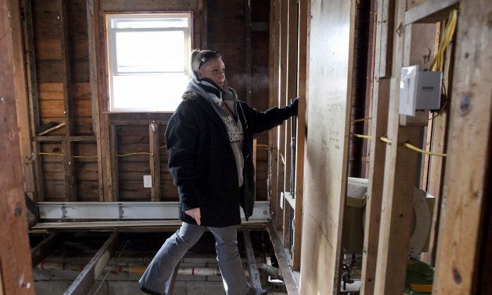 Stacey Walsh, a Build It Back applicant, navigates floor joists in her home in Broad Channel, Queens, Dec. 18, 2013. (Samira Bouaou/Epoch Times)