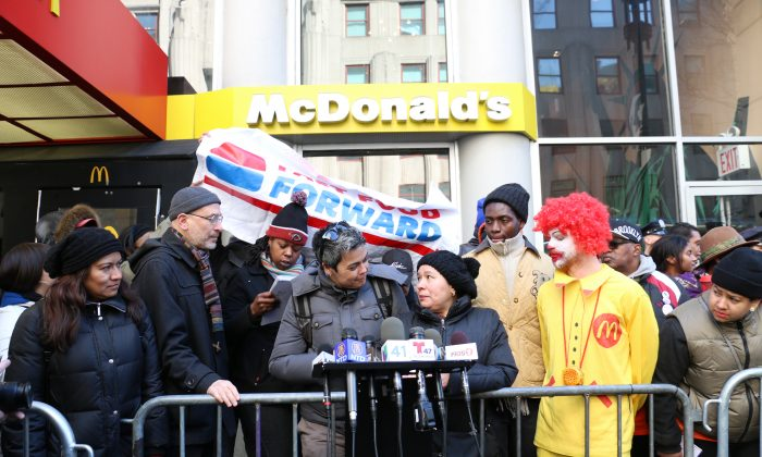 McDonald's employee Rosa Rivera (R) speaks with the help of a translator at a protest against wage theft at McDonald's in Manhattan, New York, March 18, 2014. (Allen Xie)