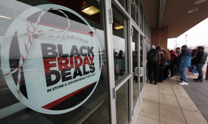 A sign promoting Black Friday specials is displayed in the window of a J.C. Penny store as shoppers queue up at the door for a 3 p.m. opening, Thursday, Nov. 26, 2015, in northeast Denver. The store opened two hours before other retailers to cash in on a flurry of bargain hunters, some who said that they waited for three hours to be one of the first people queued up outside. (AP Photo/David Zalubowski)