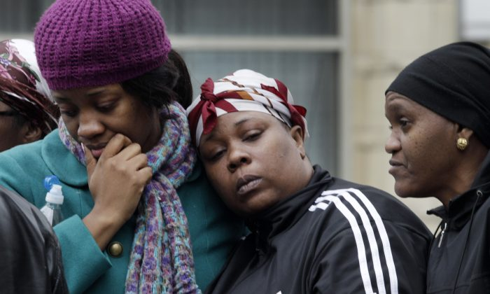 Alecia Thomas (L) is comforted by her friend Shivon Dollar (C) after she lost her home following an explosion that leveled two apartment buildings in the East Harlem neighborhood of New York, March 12, 2014. (AP Photo/Mark Lennihan)