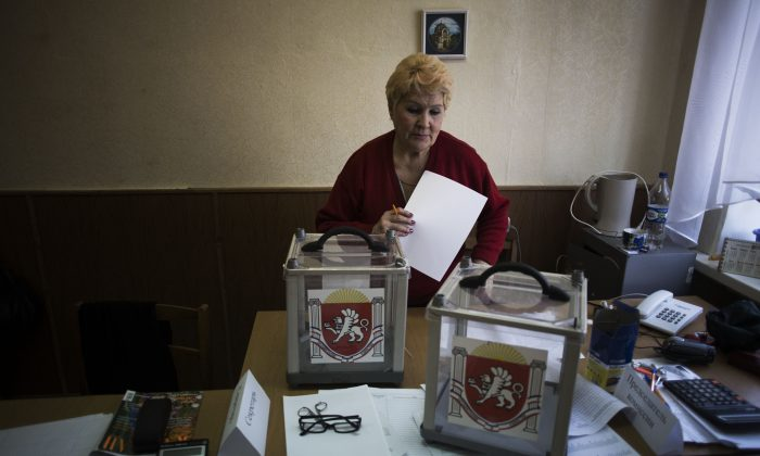 A Ukrainian woman, who is a member of the district electoral committee, makes final preparations as she stands next to ballot boxes for Sunday's referendum at a polling station in Simferopol, Ukraine, on March 15, 2014. Tensions are high in the Black Sea peninsula of Crimea, where a referendum is to be held Sunday on whether to split off from Ukraine and seek annexation by Russia. (AP Photo/Manu Brabo)