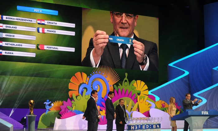 FIFA Secretary General Jerome Valcke (R and on screen) shows a paper with the name of Croatia during the final draw of the Brazil 2014 FIFA World Cup, in Costa do Sauipe, Bahia state, Brazil, on December 6, 2013. (AFP/Getty Images)