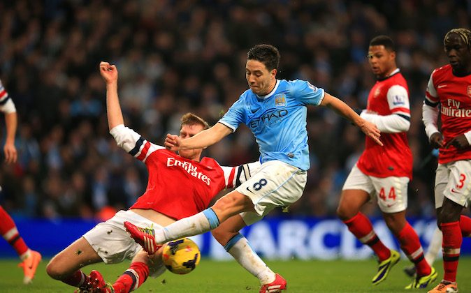 Per Mertesacker of Arsenal tackles Samir Nasri of Manchester City during the Barclays Premier League match between Manchester City and Arsenal at Etihad Stadium on December 14, 2013 in Manchester, England. (Photo by Richard Heathcote/Getty Images)
