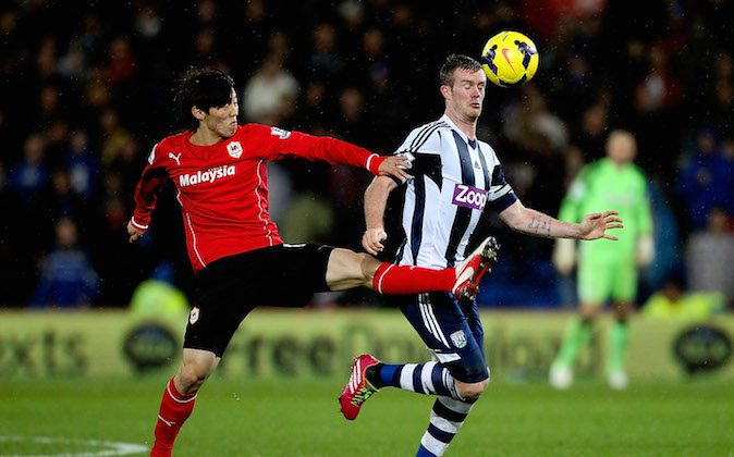 Kim Bo-Kyung of Cardiff (L) in aciton against Chris Brunt of West Brom during the Barclays Premier League match between Cardiff City and West Bromwich Albion at Cardiff City Stadium on December 14, 2013 in Cardiff, Wales. (Photo by Ben Hoskins/Getty Images)