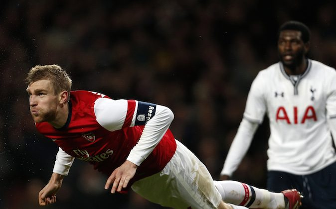 Arsenal's German defender Per Mertesacker (L) launches himself at the ball during the English FA cup third round football match between Arsenal and Tottenham Hotspur at the Emirates Stadium in London on January 4, 2014. Arsenal won the game 2-0. (AFP PHOTO/ADRIAN DENNIS)