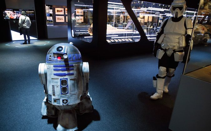 """A model of character R2-D2 (L) and a performer dressed as a scout trooper are seen during the presentation of the exhibition """"Star Wars Identities"""" at the Cite du Cinema in Saint-Denis, outside Paris, on February 13, 2014.  Divided in 3 major themes """"Origins, Influences and Choice"""" through which are explored 10 components of human identity, the exhibition displays more than 200 original pieces from the archives of Lucas Arts Museum, including models, props, costumes and sketches who built the Star Wars universe created by George Lucas. The exhibition runs through February 15 - June 30, 2014 at the Cite du Cinema, French acclaimed  director, producer and screenwriter Luc Besson's vast 170-million-euro ($230-million) """"Film City"""" studio complex. (PATRICK KOVARIK/AFP/Getty Images)"""
