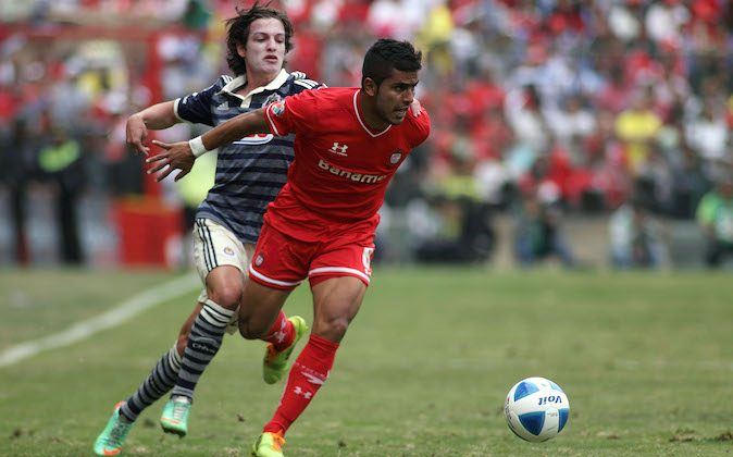 Miguel Ponce (R) of Toluca vies for the ball with Carlos Fierro (L) of Guadalajara, during their Mexican Clausura 2014 tournament football match in Mexico City, on February 23, 2014. (ADID JIMENEZ/AFP/Getty Images)