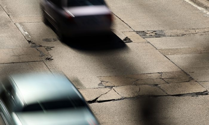 Cars travel over a section of highway riddled with potholes in Brooklyn, Feb. 24, 2014. (Spencer Platt/Getty Images)