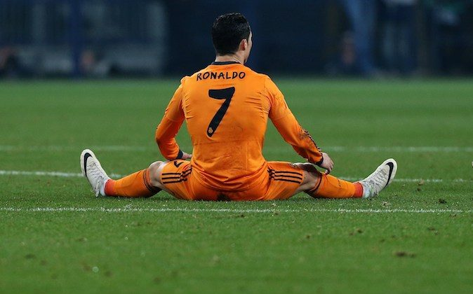 Real Madrid's Portuguese forward Cristiano Ronaldo sits on the pitch during the first-leg round of 16 UEFA Champions League football match Schalke 04 vs Real Madrid in Gelsenkirchen, western Germany on February 26, 2014. Real Madrid cruised to a rare victory on German soil as they romped to a 6-1 win at Schalke 04 in Wednesday's Champions League's last 16, first-leg clash. (RONNY HARTMANN/AFP/Getty Images)