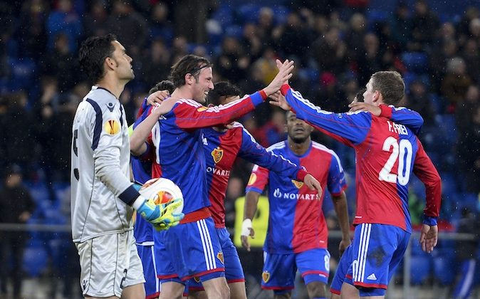 Basels players including team forward Marco Streller (2nd L) celebrate after their team's third goal as Tel-Aviv's Spanish goalkeeper Juan Pablo (L) looks on during the UEFA Europa League round of 32 second leg football match between FC Basel and Maccabi Tel Aviv FC on February 27, 2014 in Basel. (FABRICE COFFRINI/AFP/Getty Images)