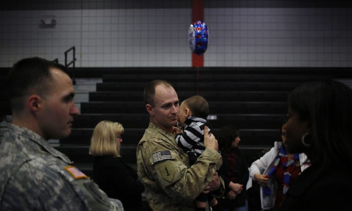 A Staff Sergeant from the U.S. Army's 3rd Brigade Combat Team, 1st Infantry Division, reunites with loved ones and family members following a homecoming ceremony in the Natcher Physical Fitness Center on Fort Knox on Thursday, February 27, 2014 in Fort Knox, Ky. (Luke Sharrett/Getty Images)
