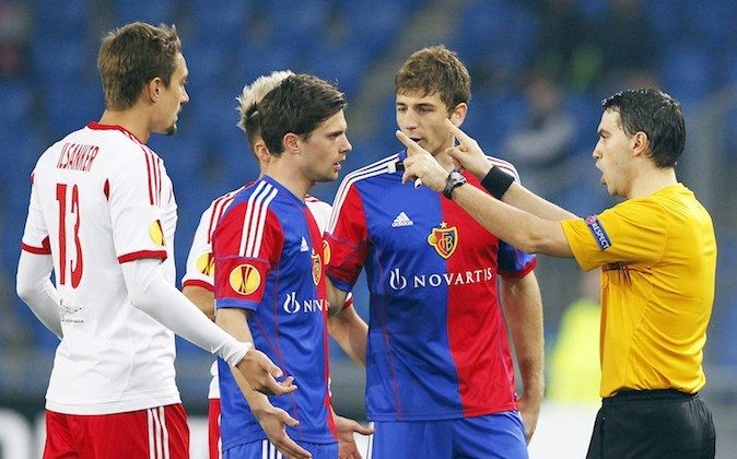 FC Basel's midfielder Valentin Stocker (2ndL) and FC Salzburg's midfielder Stefan Ilsanker (L) argue with Romanian referee Ovidiu Alin Hategan (R) during the UEFA Europa League round of 16 first leg football match between FC Basel and FC Salzburg on March 13, 2014 in Basel. (MICHAEL BUHOLZER/AFP/Getty Images)