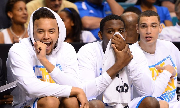 Kyle Anderson #5, Norman Powell #4 and Zach LaVine #14 of the UCLA Bruins react on the bench as they watch teammates play late in their semifinal game of the Pac-12 Basketball Tournament against the Stanford Cardinal at the MGM Grand Garden Arena on March 14, 2014 in Las Vegas. UCLA won 84-59. (Ethan Miller/Getty Images)
