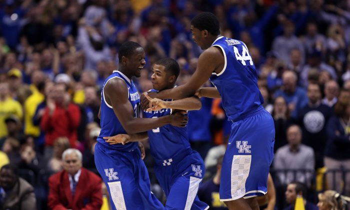 Aaron Harrison #2 of the Kentucky Wildcats celebrates with teammates Julius Randle #30 and Dakari Johnson after defeating the Michigan Wolverines 75 to 72 in the midwest regional final of the 2014 NCAA Men's Basketball Tournament at Lucas Oil Stadium on March 30, 2014 in Indianapolis, Indiana. (Jonathan Daniel/Getty Images)