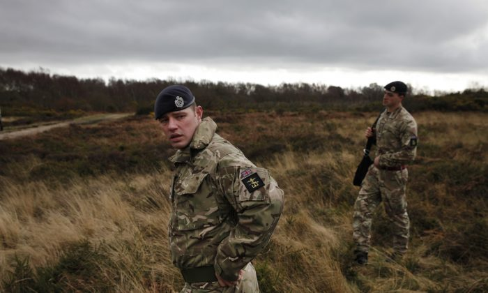 British army officers walk on an area with WW1 practise trenches in Gosport, southern England, Thursday, March 6, 2014. (AP Photo/Lefteris Pitarakis)