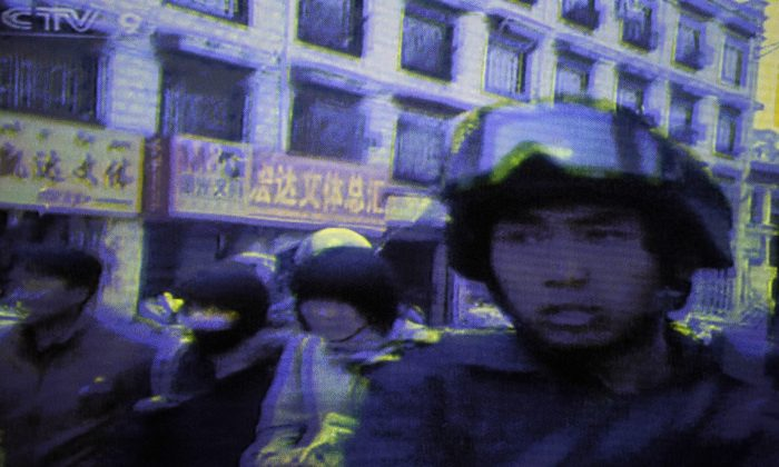 A frame-grab taken from China's state television CCTV shows armed soldiers on a street in the Tibetan capital, Lhasa, on March 16, 2008, a few months before the Beijing Olympics. Tibetan groups report that the Chinese regime violently cracked down on protests throughout Tibet at that time, resulting in an unknown number of deaths and disappearances. (AFP/AFP/Getty Images)