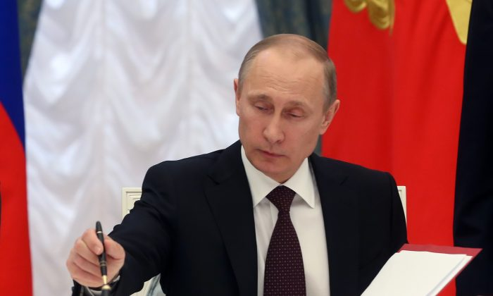 In this March 21, 2014, photo, Russian President Vladimir Putin signs bills making Crimea part of Russia in the Kremlin in Moscow. (AP Photo/Sergei Chirikov)