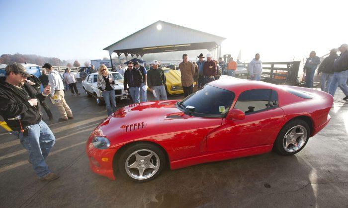 Auctioneers move a Dodge Viper car before a public auction Friday, Nov. 20, 2009. (AP Photo/Jason E. Miczek)