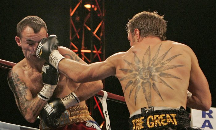 Australia's Michael Katsidis, right, throws a punch at Britain's Kevin Mitchell during their boxing match for the interim WBO lightweight championship of the world at Upton Park in London, Saturday, May 15, 2010. (AP Photo/Akira Suemori)